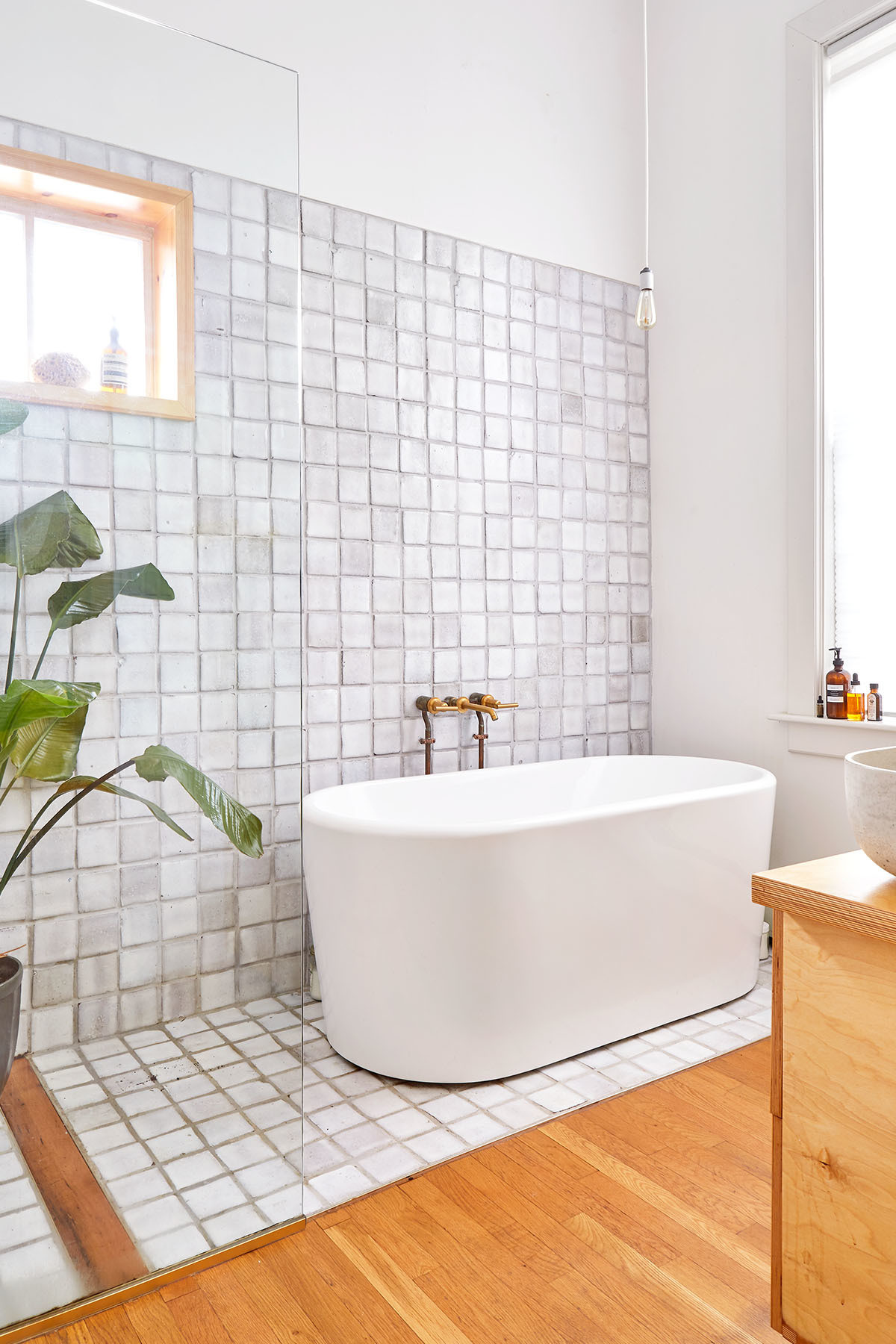The couple opted to carve out bedroom space to create a contemporary master bath, complete with vintage wall tiles that date back to the 1970s.Wayfair Bath |Kohler Hardware.