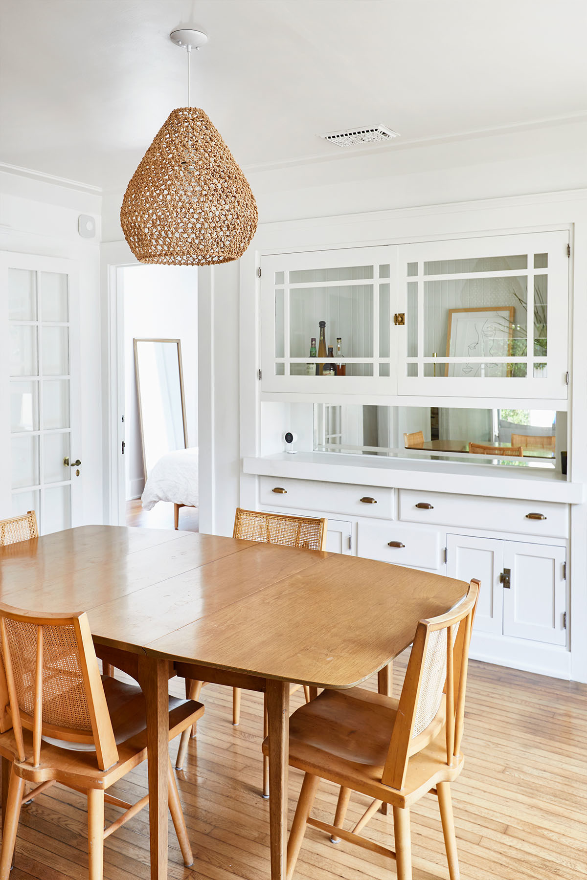 A contemporary-cool dining space boasts glass cabinetry, a wet bar, and a vintage Russel Wright dining table and chairs. Etsy Pendant Light.