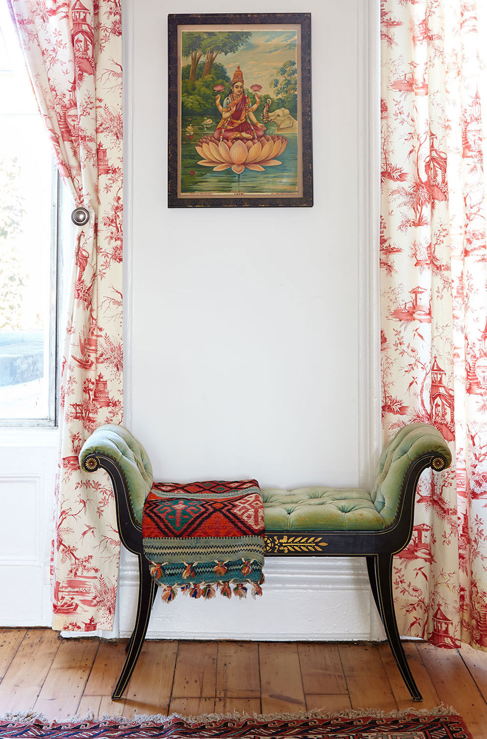 A settee in the dining room is framed by eye-catching drapery.
