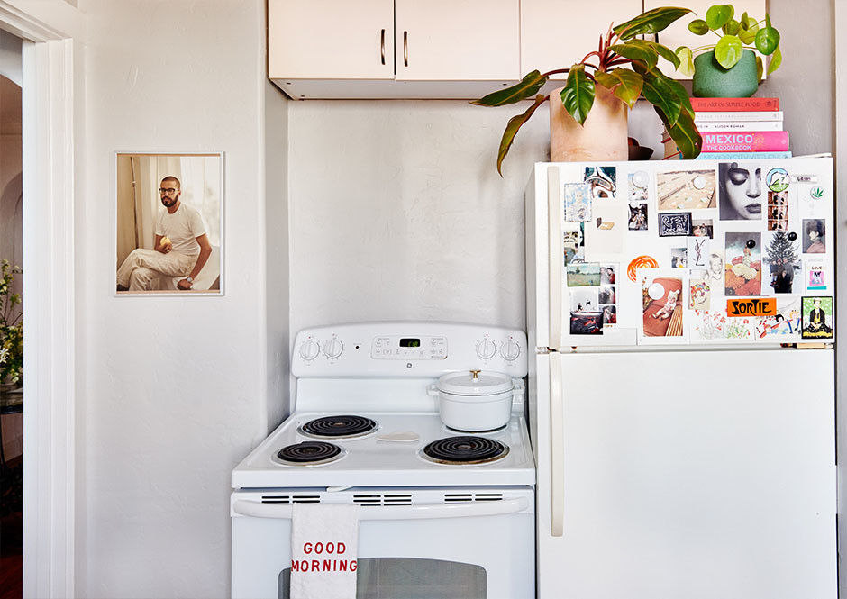 The kitchen — a characteristically tiny space — doesn't deter the couple from cooking and hosting at home. Chris Behroozian Print | Staub Dutch Oven | Jenny Pennywood Tea Towel | CB2, Flora Grubb Planters.