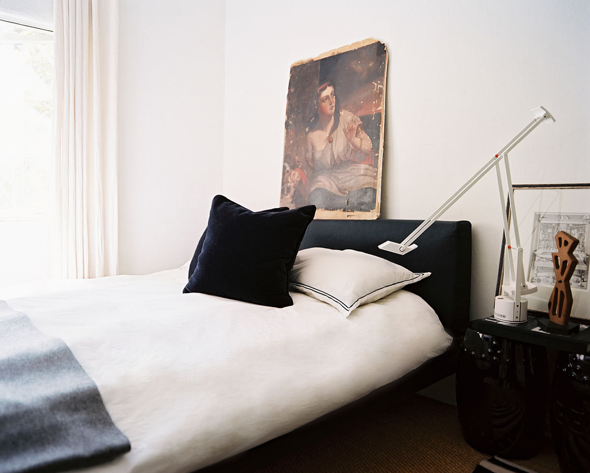 "Light-colored walls and sisal carpeting lend the bedroom a relaxed, fresh feeling. An antique fresco is propped against the wall. ""Leaning art against a wall creates a less formal, gallery-like vibe,"" says Straus."