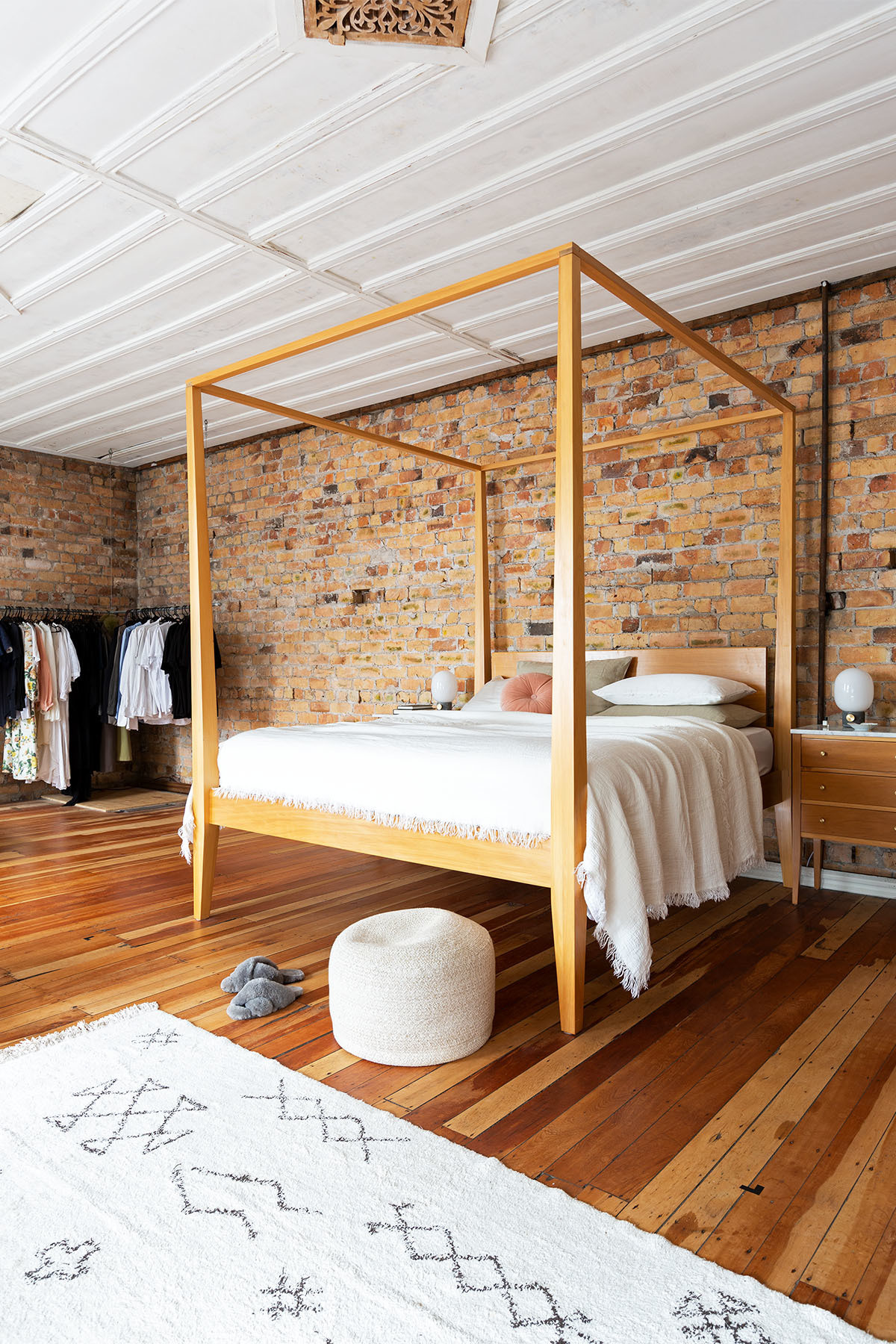 A warm, minimal bedroom aesthetic maximizes space and celebrates the hall's original features, like the exposed brick walls and ceiling detailing. Vintage Bed | Penney & Bennett, Wallace Cotton, Città Bedding | Città Throw | Kmart Pouf | Vintage Nightstands | Menu Lamps | Custom Clothes Rack.