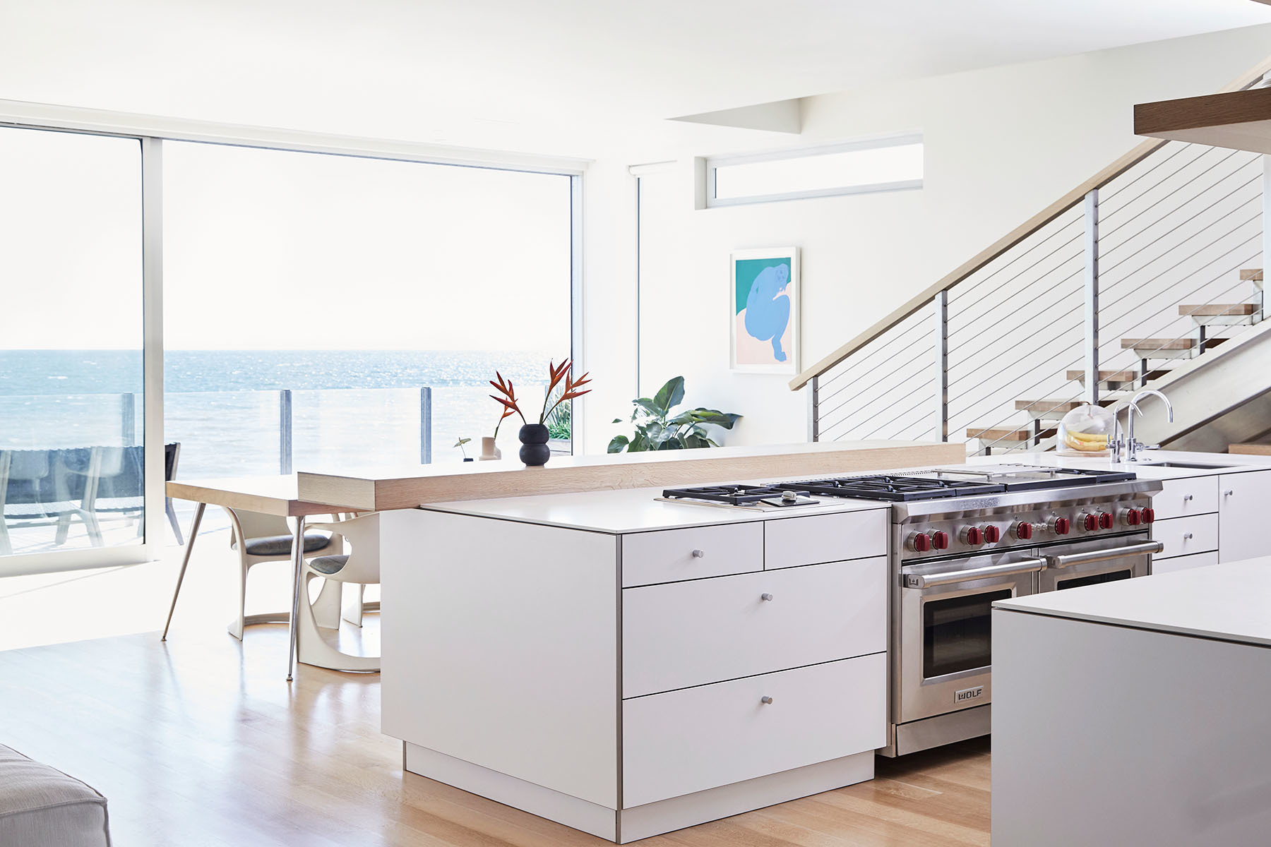 The beachfront home of Lunya founder, Ashley Merrill, exudes minimalism. Unvarnished Custom Dining Table | Ostergaard Vintage Dining Chairs | Piero Passacantando Artwork via Uprise Art | Wolf Appliances.