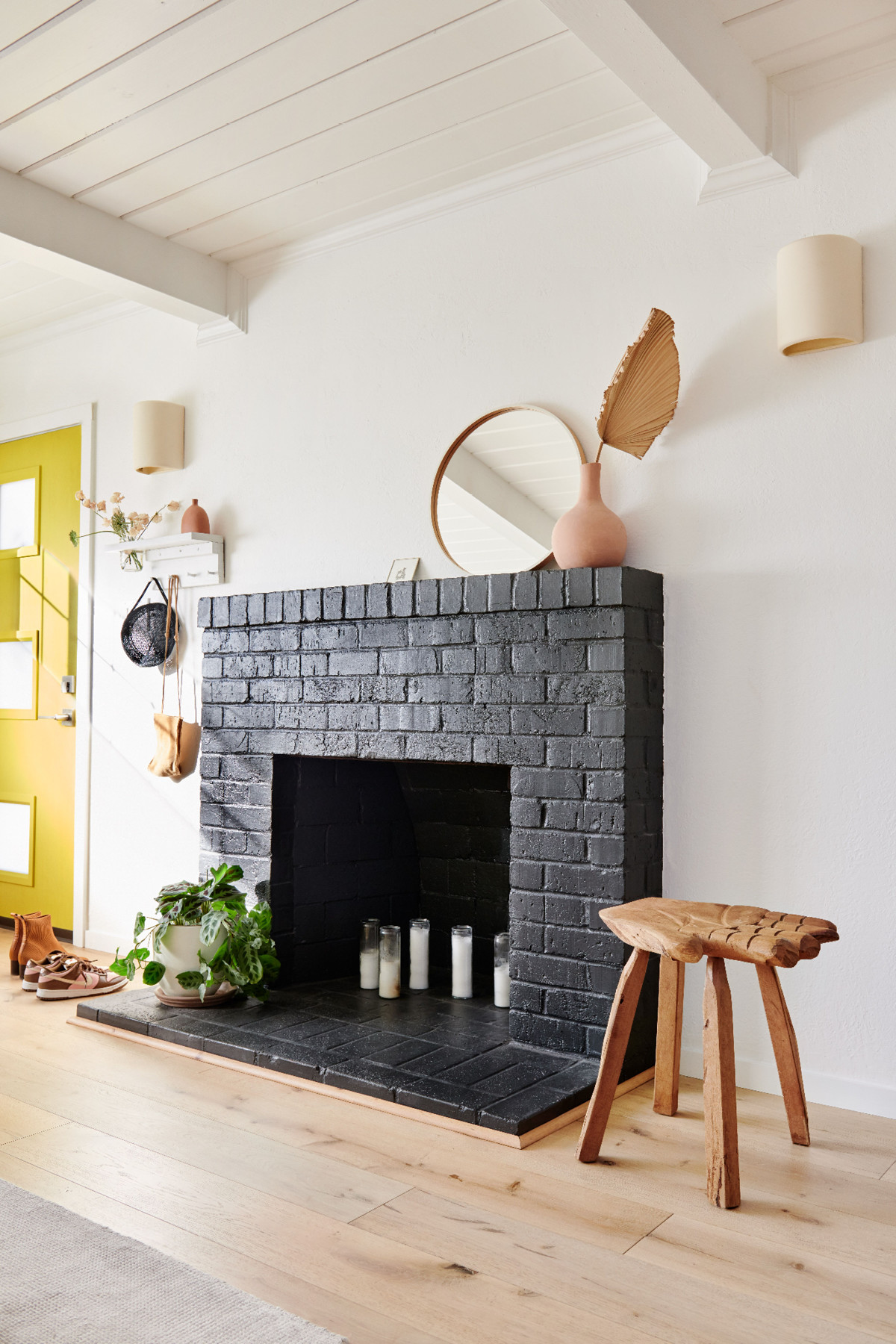 The living room's fireplace is painted an inky tone and is peppered with personal items, including one of del Rio's favorites — the hand-carved stool she acquired in Mexico.