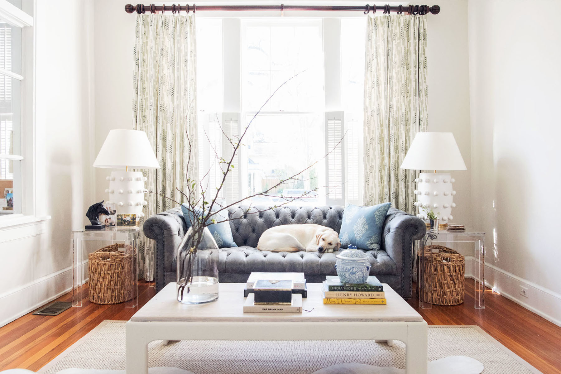 Weeziefounder Liz Eichholz's Savannah home oozes southern charm, Lola the lab curls up on the sofa. Antique ChesterfieldSofa |Schumacher Pillows |Scott Antique Market Coffee Table | Clutter; Fieldshop at The DewberryAccent Pieces |Target Vase|Safavieh Rug |Scott Antique Market Hide |Ballard Design Acrylic Side Tables |Kelly Wearstler Lamps |The Paris Market Horse Head Candle |HomeGoods Cane Baskets |Thomas Callaway Custom Drapes.